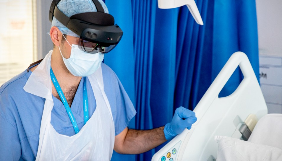 An NHS doctor at St. Mary's Hospital speaks with a patient on a COVID-19 ward during the pandemic whilst wearing a Microsoft Hololens